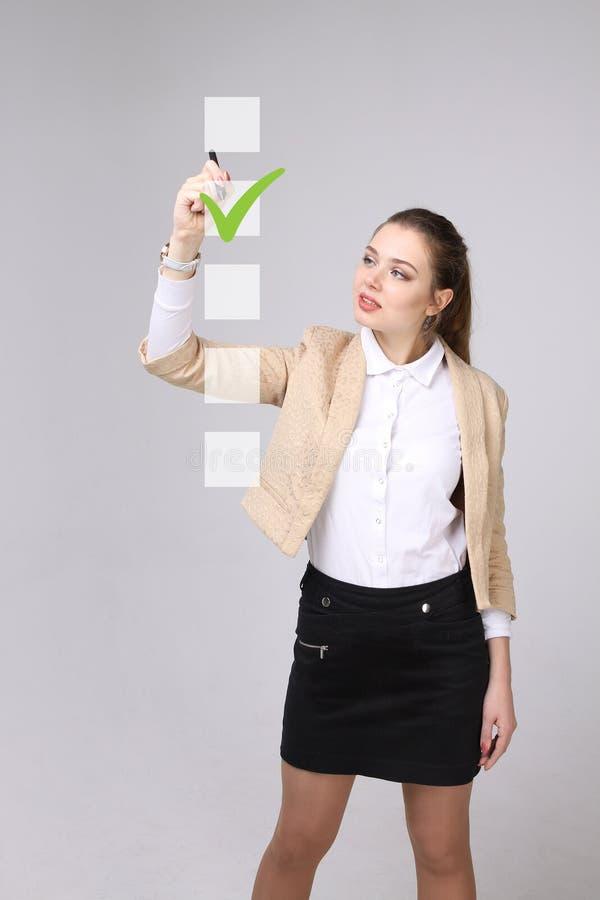 Jonge bedrijfsvrouw die op controlelijstdoos controleren Grijze achtergrond royalty-vrije stock foto's