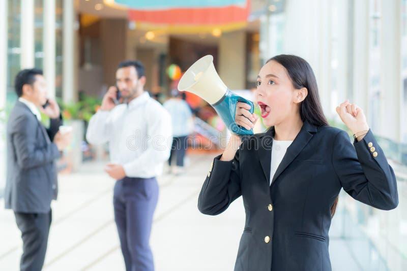 Jonge bedrijfsvrouw die op het kantoor werken, en in megafoon schreeuwen schreeuwen stock foto's