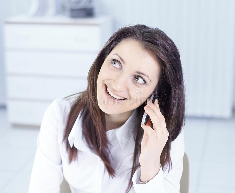 Jonge bedrijfsvrouw die op mobiele telefoon in bureau spreken stock foto
