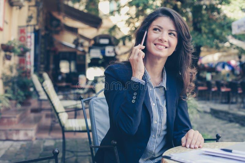 Jonge bedrijfsvrouw die op slimme telefoon spreken royalty-vrije stock afbeeldingen