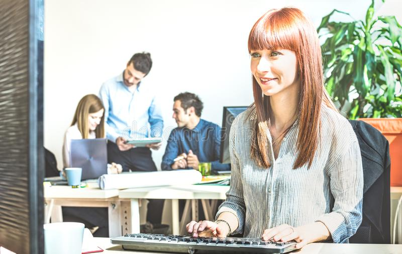 Jonge bedrijfsvrouw die pret hebben die bij computer met coworke werken royalty-vrije stock afbeeldingen