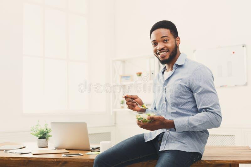 Jonge bedrijfsvrouw die salade eten op kantoor royalty-vrije stock foto