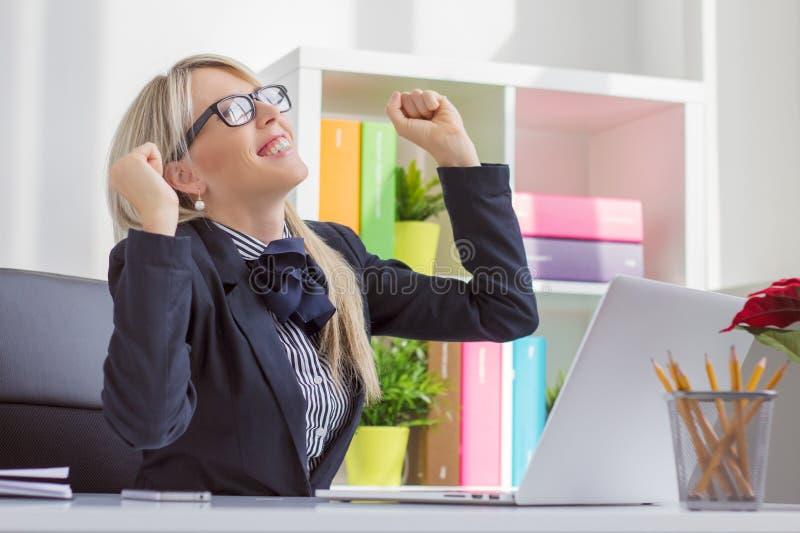 Jonge bedrijfsvrouw die van succes genieten op het werk stock foto's