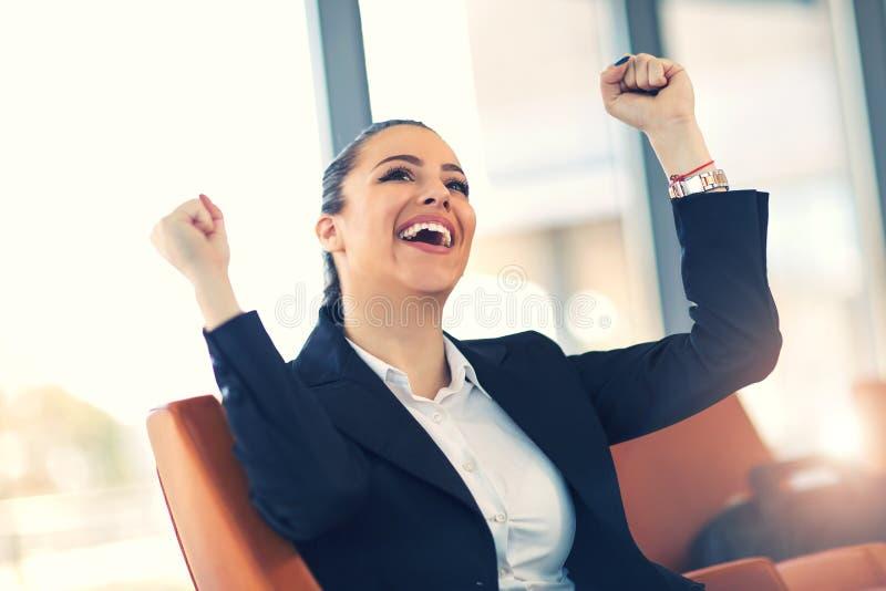 Jonge bedrijfsvrouw die van succes genieten op het werk royalty-vrije stock afbeelding