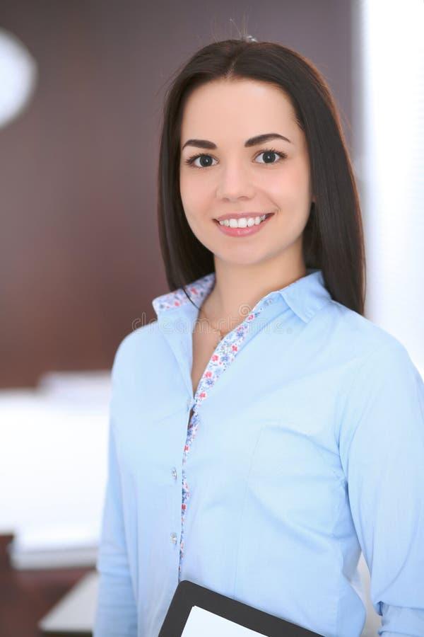 Jonge bedrijfsvrouw die zich in bureau bevindt royalty-vrije stock afbeeldingen