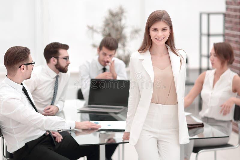 Jonge bedrijfsvrouw die zich dichtbij haar Bureau bevinden stock foto's