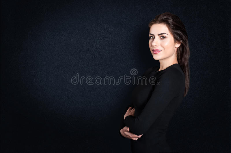 Jonge bedrijfsvrouw die zich ernstig tegen zwarte achtergrond bevinden royalty-vrije stock fotografie