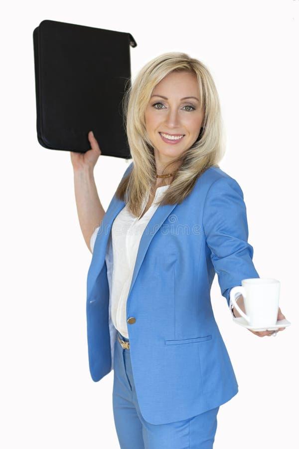 jonge bedrijfsvrouw in een jasje met een bureauomslag en een Kop van koffie, een vrouw van het bedrijfsportretblonde in een blauw stock foto's