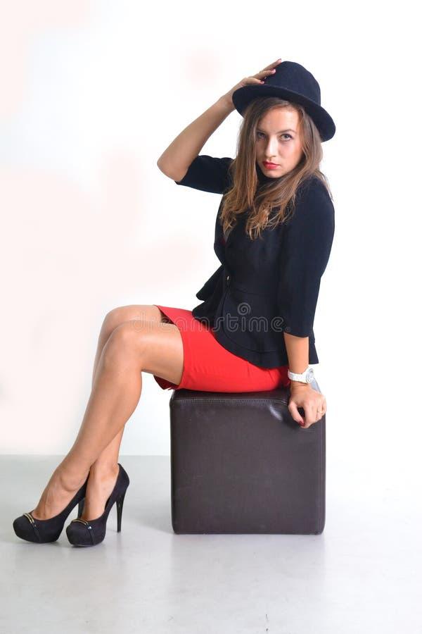 Jonge bedrijfsvrouw in een rode rok en een zwart jasje royalty-vrije stock fotografie