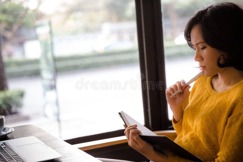 Jonge bedrijfsvrouw in gele kledingszitting bij lijst in koffie stock afbeelding
