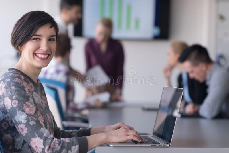 Jonge bedrijfsvrouw op kantoor die aan laptop met team op me werken royalty-vrije stock afbeeldingen