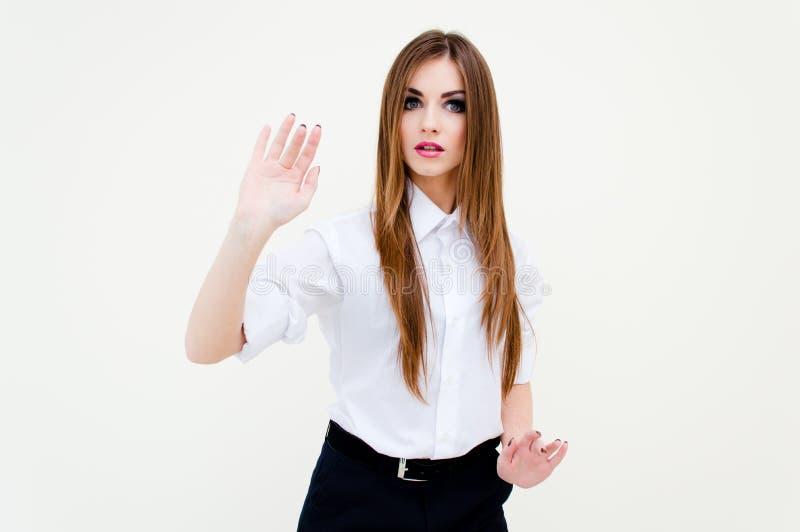 Jonge bedrijfsvrouw wat betreft het virtuele scherm op wit stock foto
