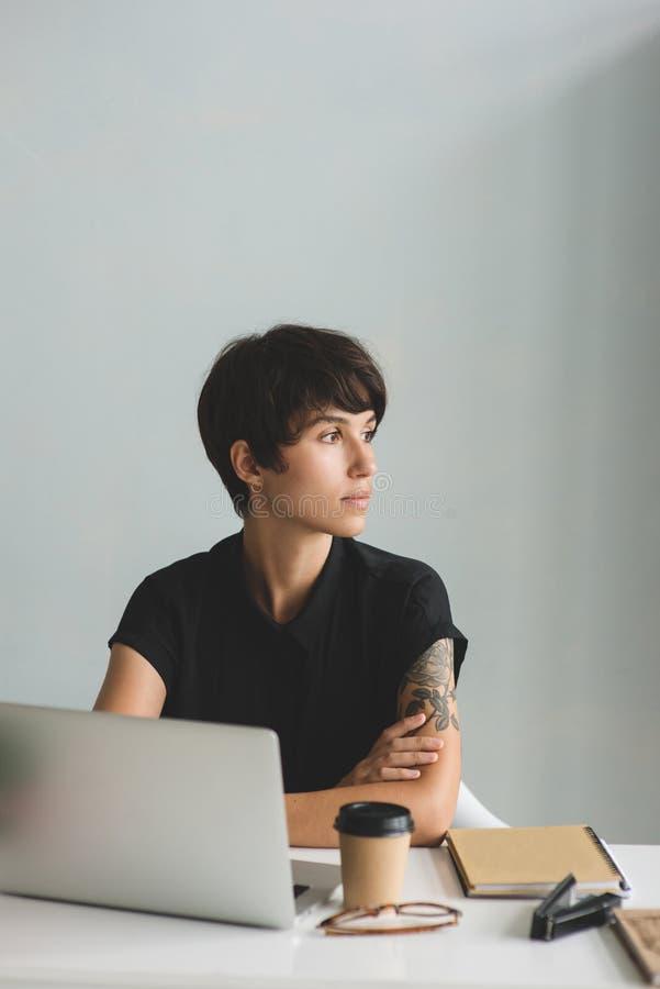 Jonge bedrijfsvrouwenzitting bij het bureau met gekruist en wapens die weg eruit zien stock foto's