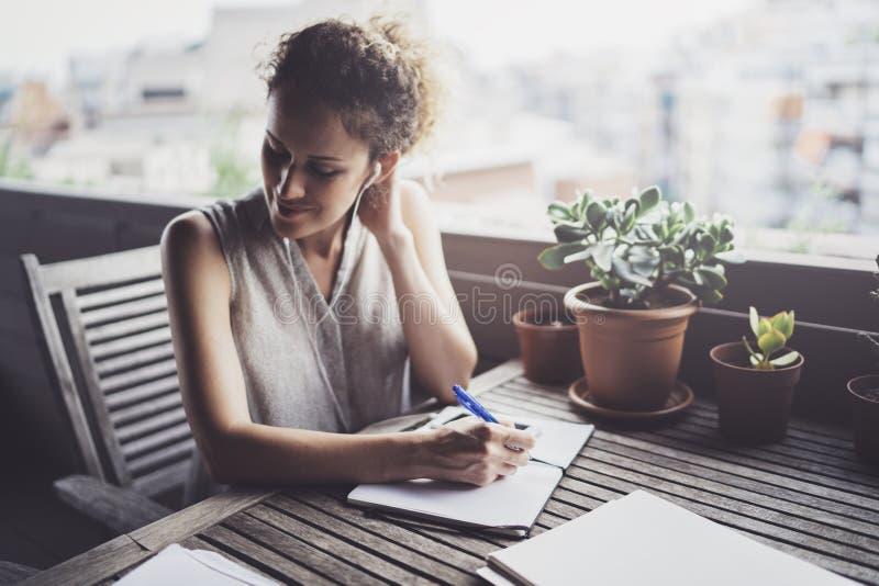 Jonge bedrijfsvrouwenzitting bij lijst in caffee terras en het nemen van nota's in notitieboekje Op lijst is smartphone en docume royalty-vrije stock afbeelding