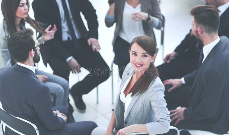 Jonge bedrijfsvrouwenzitting in een cirkel van collega's royalty-vrije stock afbeeldingen