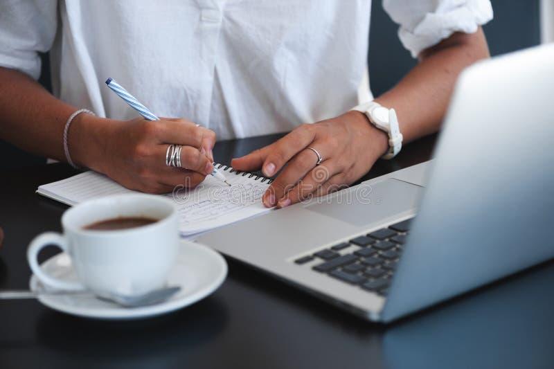 Jonge bedrijfsvrouwenzitting in koffie en het nemen van nota's in notitieboekje stock fotografie