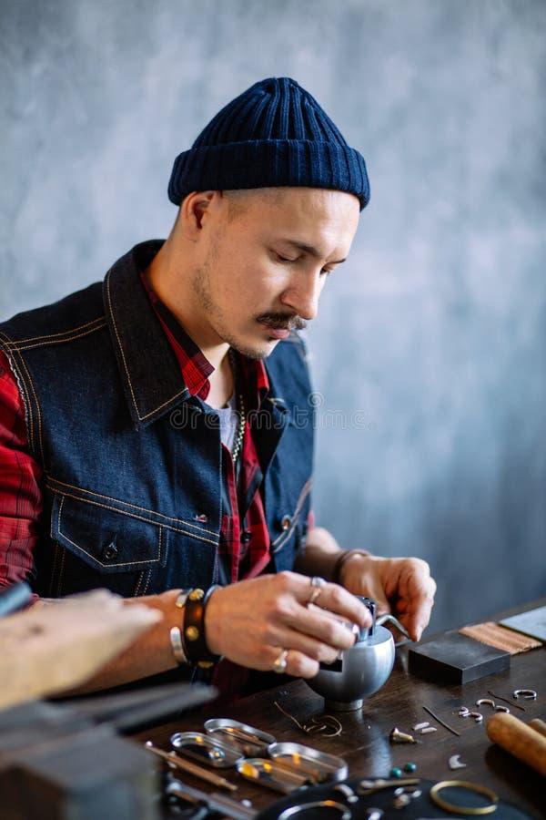 Jonge begaafde vakman die gravureblok gebruiken Juwelentoebehoren stock afbeelding