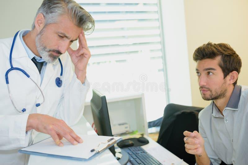 Jonge beklemtoonde mannelijke patiënt die arts raadplegen royalty-vrije stock foto's