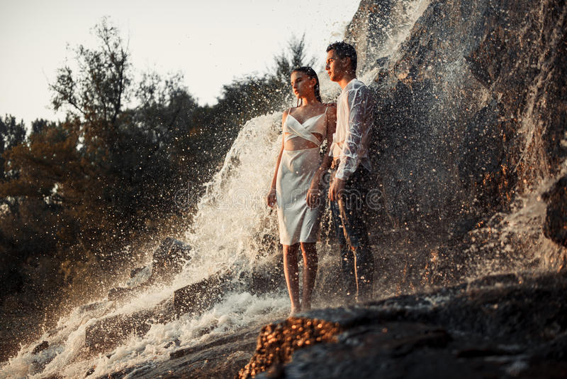 Jonge bekoorde paartribunes op rots onder nevel van waterval stock foto's