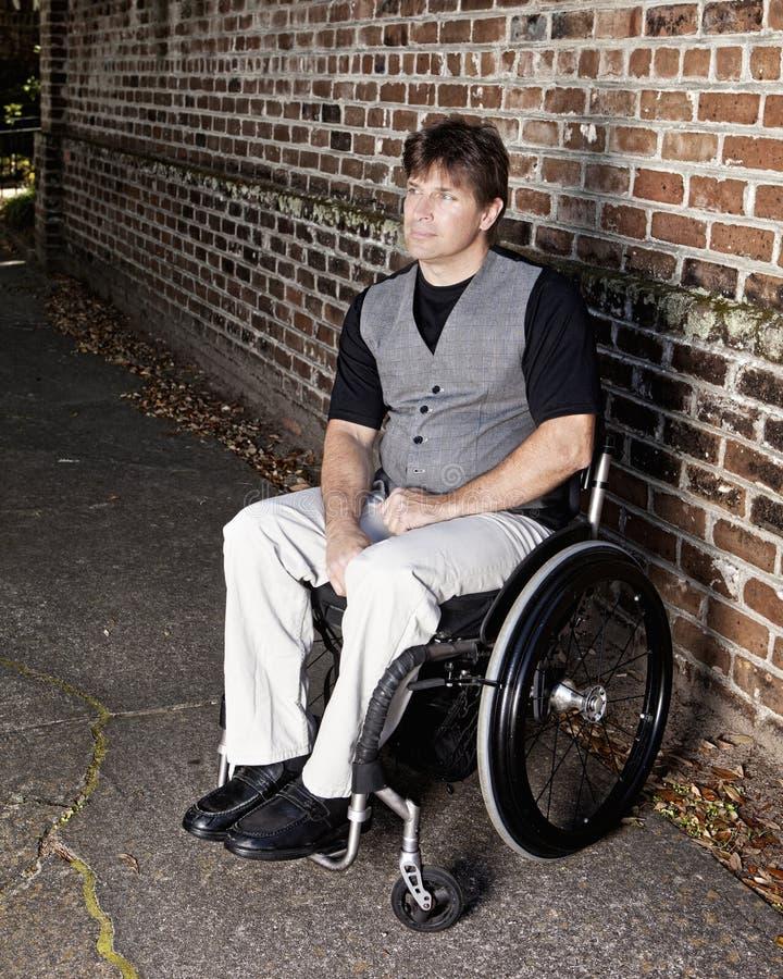 Jonge bepaalde mens in rolstoel stock afbeelding