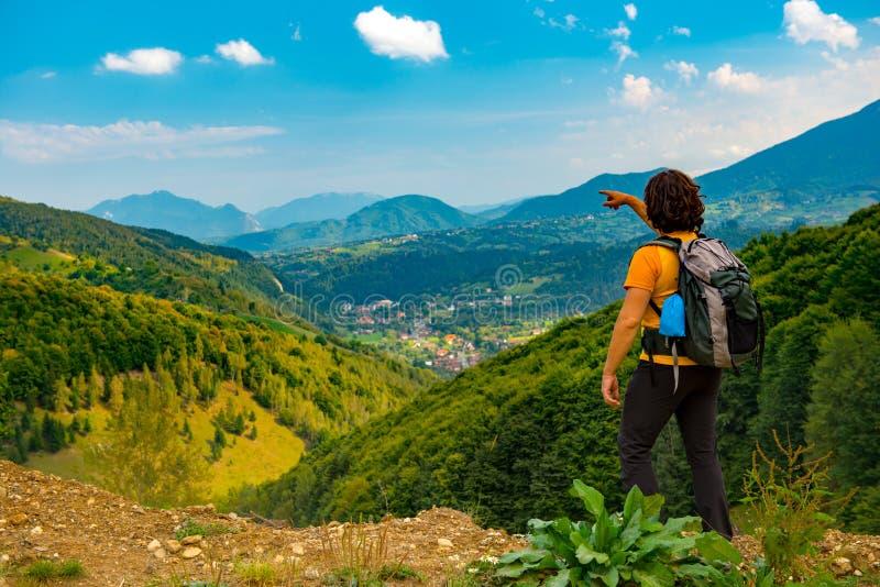 Jonge bergwandelaar die aan een mooi die berglandschap richten met weelderige bossen wordt behandeld Wandeling in een zonnige de  royalty-vrije stock foto