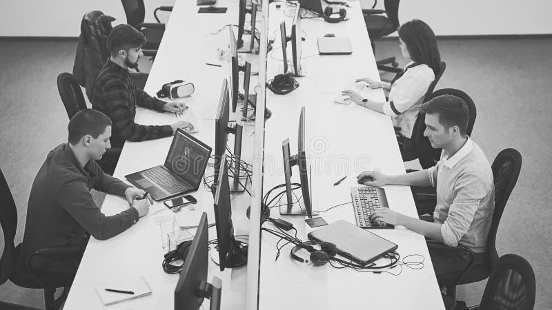 Jonge beroeps die in modern bureau werken De groep ontwikkelaars of programmeurs die bij bureaus zitten concentreerde zich op com stock afbeeldingen