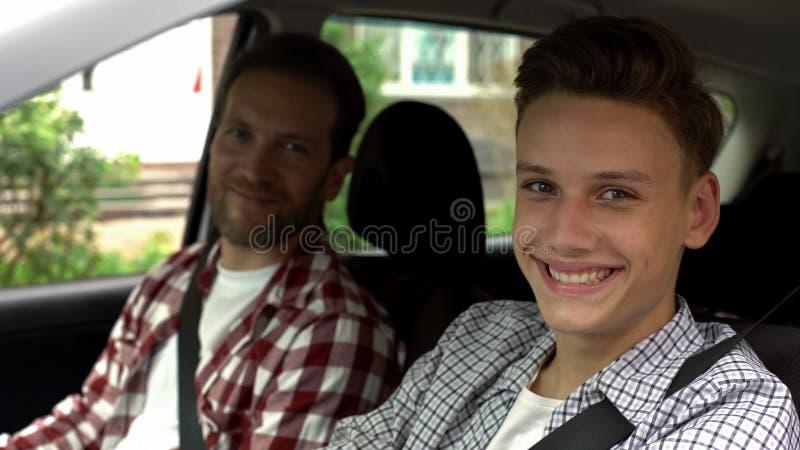 Jonge bestuurder en zijn vader die in camera, tiener glimlachen die rijbewijs krijgen stock afbeeldingen