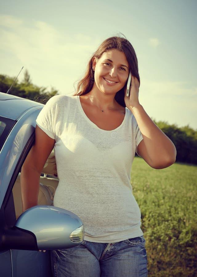 Jonge Bestuurder Woman op de telefoon door auto stock foto