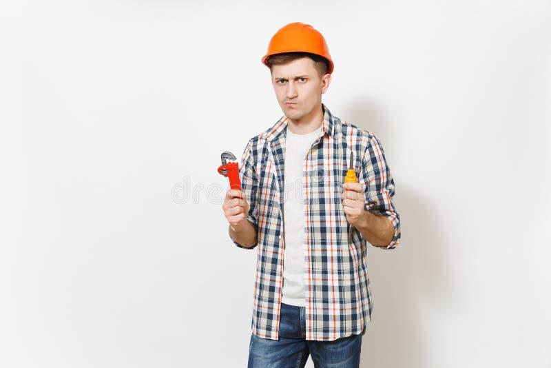 Jonge betrokken knappe mens in beschermende oranje het stuk speelgoed van de bouwvakkerholding geïsoleerde schroevedraaier en reg stock fotografie