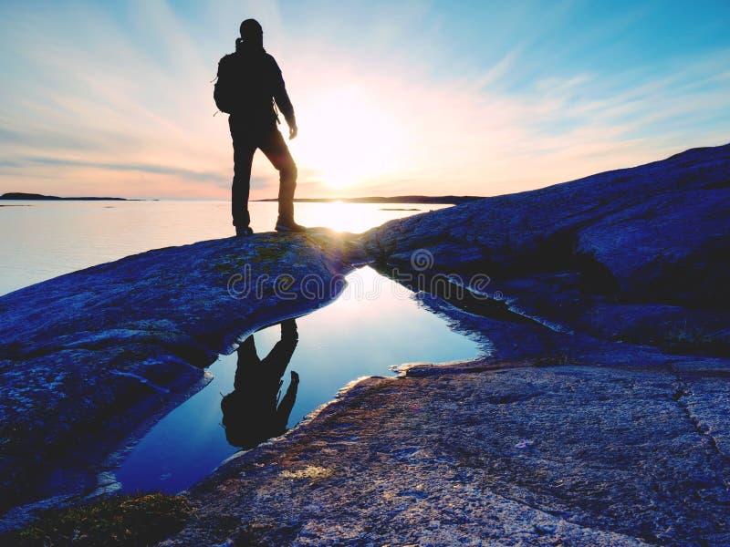 Jonge bevindende mens met rugzak Wandelaar op de steen op de kust bij kleurrijke zonsonderganghemel royalty-vrije stock foto