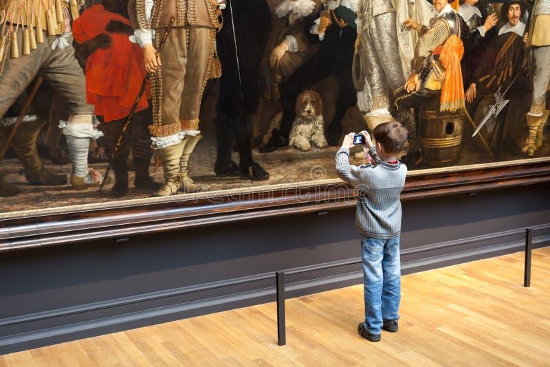 Jonge bewonderaar van het beroemde schilderen van Rembrandt stock foto
