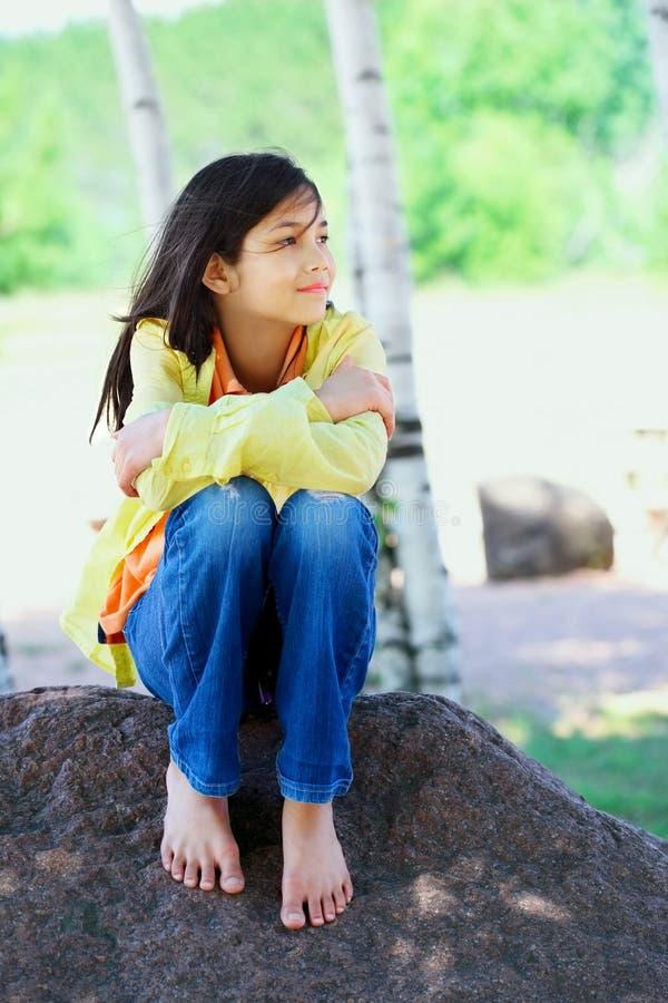 Jonge biracial meisjeszitting op rots onder bomen stock foto