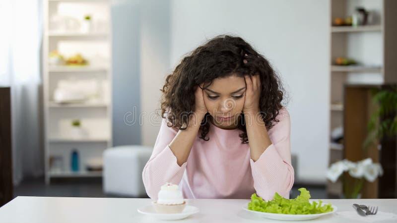 Jonge biracial vrouw die tussen salade en snoepjes, gezondheidszorgkeus kiezen royalty-vrije stock fotografie