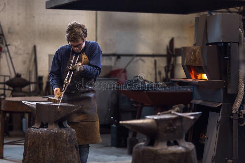 Jonge blaksmith die met heet metaal in een workshop werken royalty-vrije stock foto