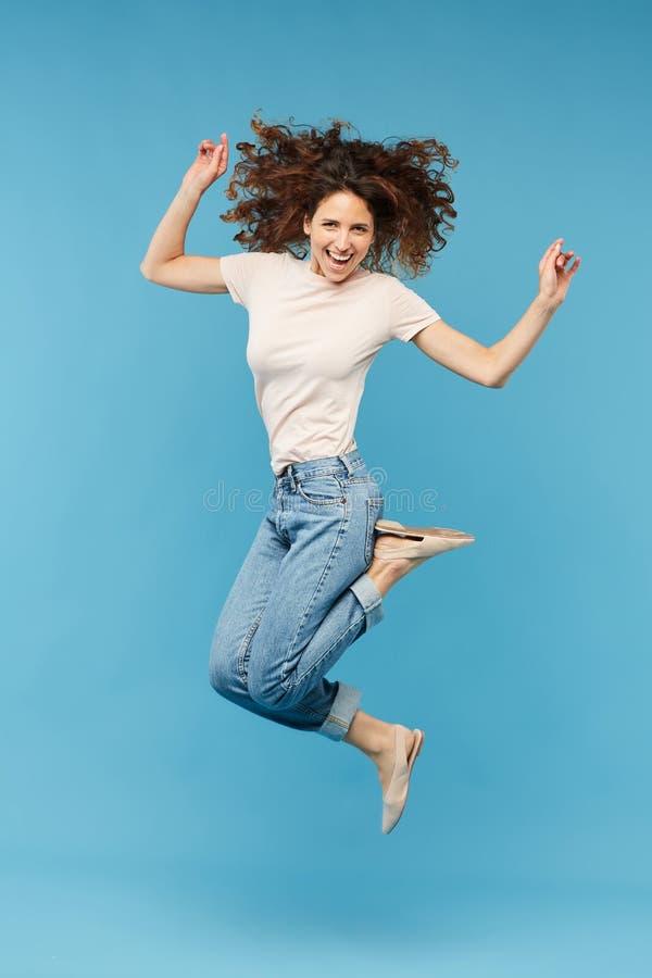 Jonge blije donkerbruine vrouw die afzonderlijk springen stock foto's