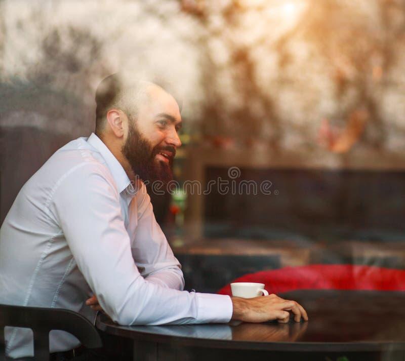 Jonge blije dromerige mannelijke zakenman in koffie, mening door venster met bezinningen over glas royalty-vrije stock foto