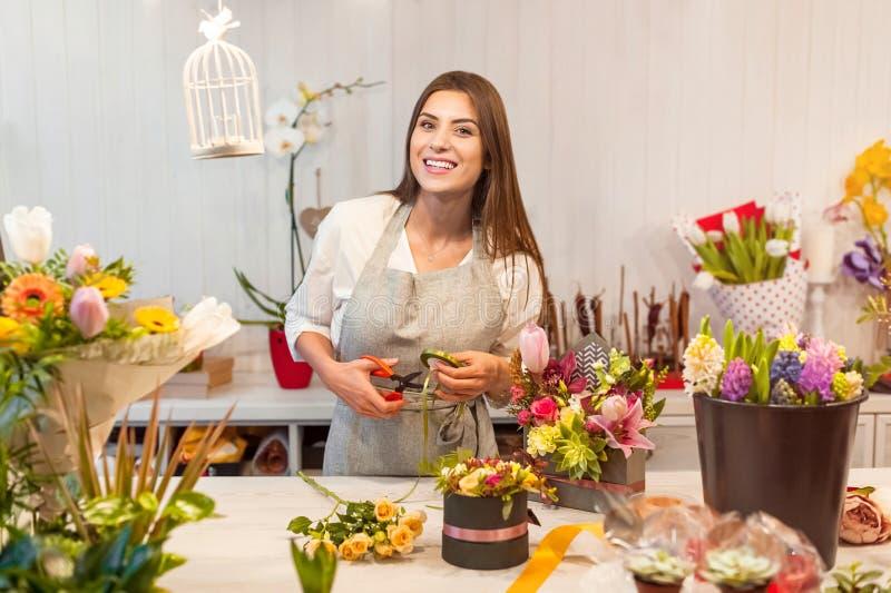 Jonge bloemistvrouw in een bloemwinkel stock afbeelding