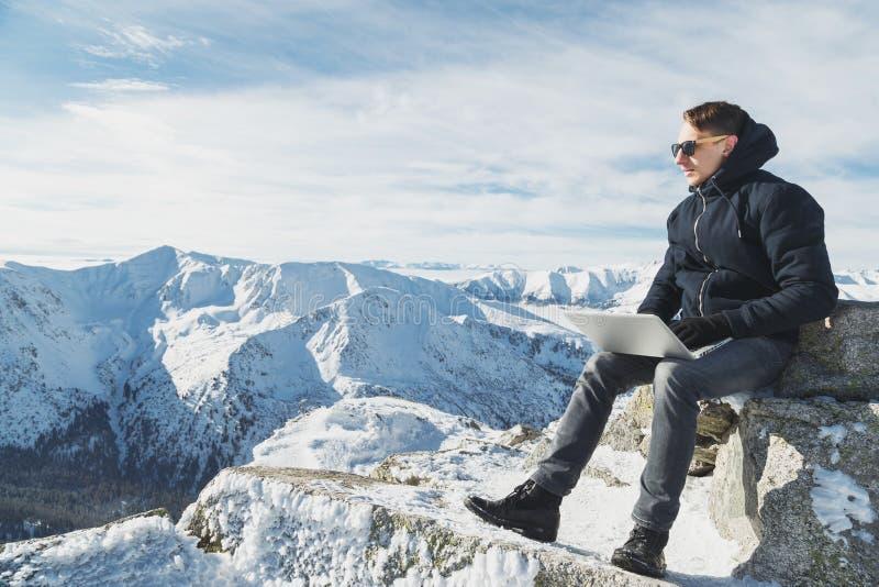 Jonge blogger of freelancer het werken aan laptop bovenop de wereld De winter lanscape in zonnige dag stock afbeelding