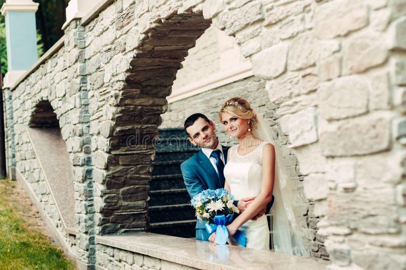 Jonge blonde bruid en haar bruidegomtribune in een exotisch park royalty-vrije stock foto's