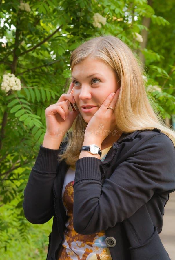 Jonge blonde dame die via mobiele telefoon spreekt royalty-vrije stock afbeeldingen