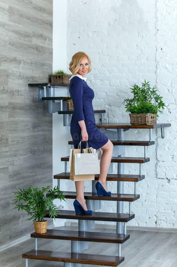 Jonge blonde elegante vrouw met het winkelen zakken op de treden royalty-vrije stock afbeelding