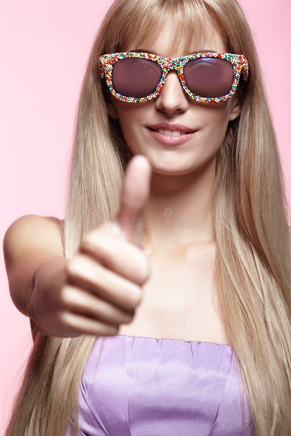Jonge blonde glimlachende vrouw met omhoog de glazen en de duim van het pretsuikergoed stock foto