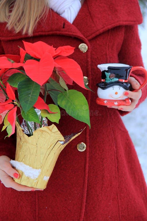 Jonge blonde-haired vrouw die in rode laag de leuke kop van de sneeuwmankoffie en Poinsettiainstallatie houden stock afbeelding