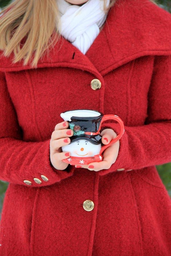 Jonge blonde-haired vrouw die in rode laag de leuke kop van de sneeuwmankoffie houden stock afbeeldingen
