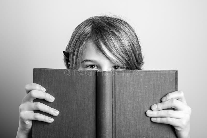 Jonge blonde het glimlachen kerel met boek zwart-witte foto royalty-vrije stock afbeelding