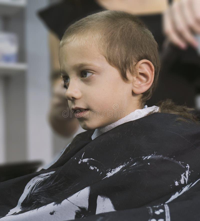 Jonge blonde jongen die een kapsel krijgen royalty-vrije stock afbeeldingen