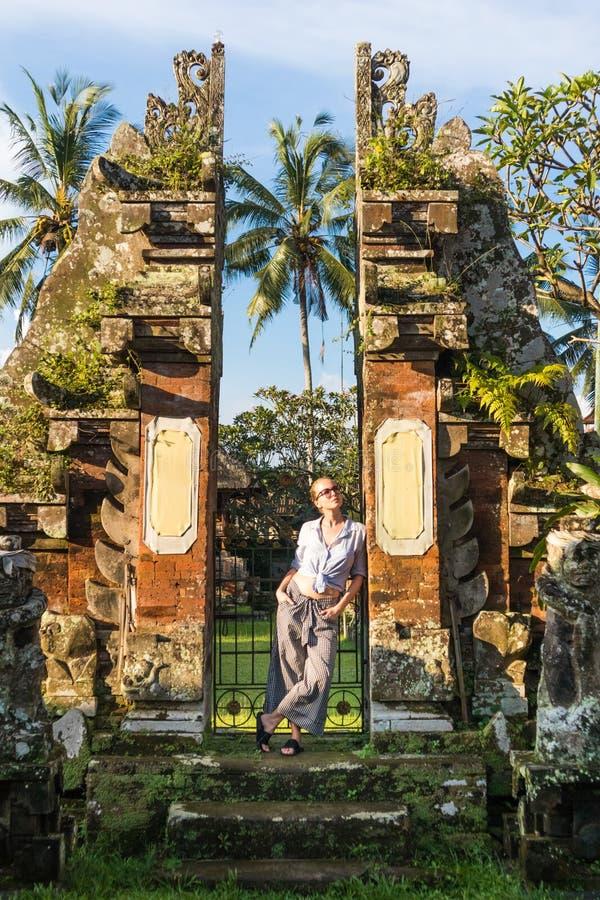 Jonge blonde Kaukasische vrouw die en traditionele hidu reizen onderzoeken tamples rond Ubud op Bali stock fotografie