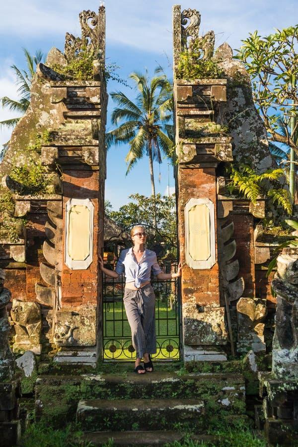 Jonge blonde Kaukasische vrouw die en traditionele hidu reizen onderzoeken tamples rond Ubud op Bali royalty-vrije stock fotografie