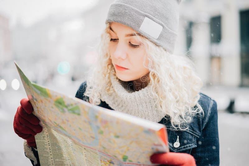 Jonge blonde krullende meisjestoerist met kaart royalty-vrije stock foto