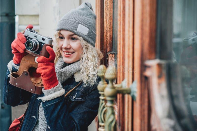 Jonge blonde krullende vrouwelijke het schieten foto op oude filmcamera stock fotografie